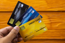 The Image Of A Person Holding A Yellow, Blue, And Black Credit Card With A Wooden Wall Background Suitable For Use With Content.
