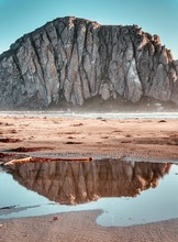 Morro Rock With A Reflection From A Puddle.