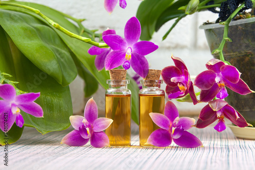 Fototapety, obrazy: Essence of  orchid flowers on table in beautiful glass jar