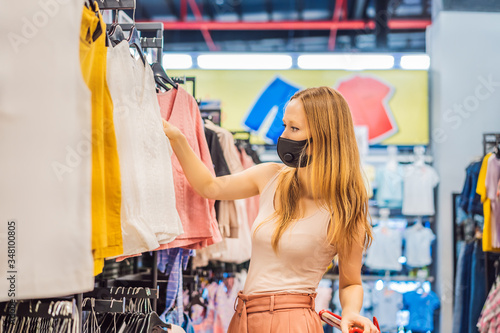 Cuadros en Lienzo Woman in a clothing store in a medical mask because of a coronovirus