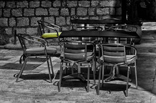 Empty Chairs By Table On Sidewalk Cafe
