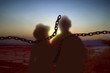 Broken chain with the silhouette of a couple standing in the morning