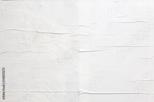White crumpled wavy paper poster glued on billboard texture background. Copy space for text.