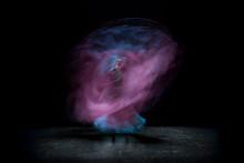 Blurred Motion Of Ballet Dancer Against Black Background