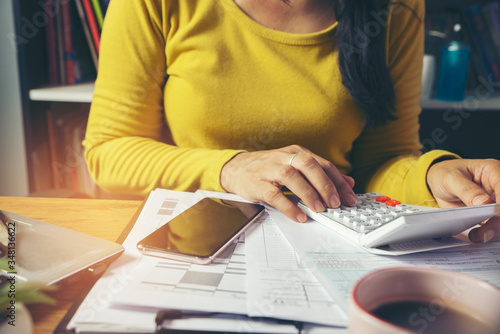 Fotomural Budget planning concept, Accountant calculating tax and using mobile phone, work online at home