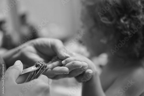 Fotografia Cropped Image Of Mother Hand Cutting Daughter Fingernails