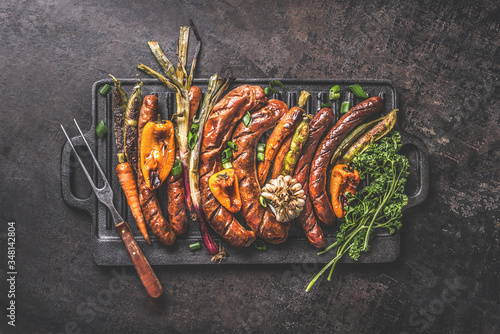 Fototapeta Various grilled meat sausages with roasted vegetables on cast iron grill pan with meat fork on dark rustic background. Grill party Oktoberfest German food. Top view. Traditional cuisine obraz