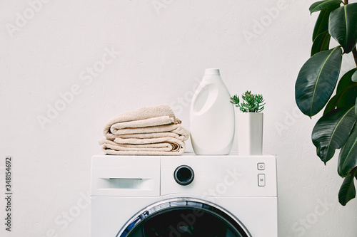 Photo detergent bottle and towels on washing machine and green plant in bathroom