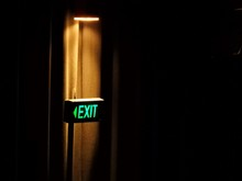 Illuminated Exit Sign On Doorway In Movie Theater