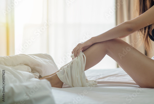 Woman taking off her white panties lying on white bed.