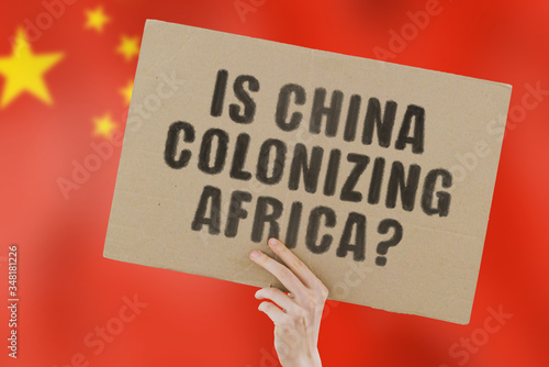 The question  Is china colonizing Africa?  on a banner in men's hand with blurred Chinese flag on the background Canvas Print