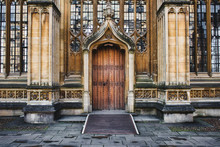 Exterior Of The Divinity School In Oxford Showing A Big Wooden Door Entrance And Columns And Stained Glass Windows