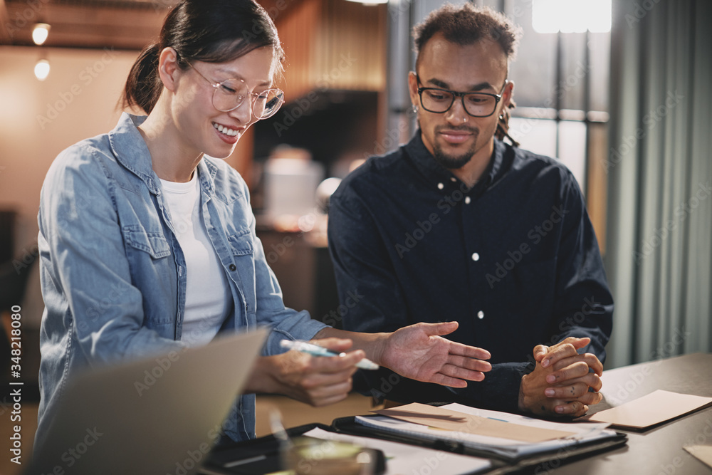 Fototapeta Diverse young businesspeople smiling while working together in a