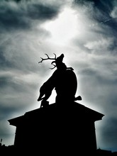 Low Angle View Of Silhouette Stag Statue Against Cloudy Sky