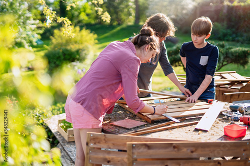 Fotografie, Obraz A mother and her two children build wooden planters for their permaculture veget