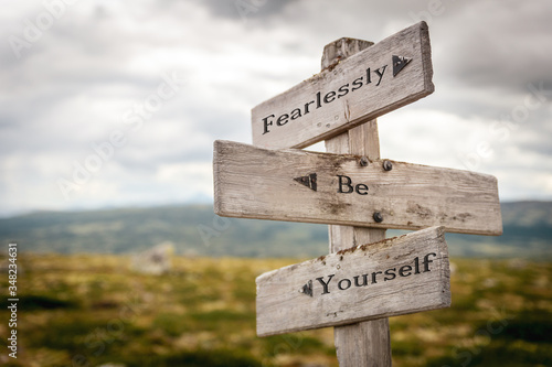 fearlessly be yourself text engraved on old wooden signpost outdoors in nature Wallpaper Mural