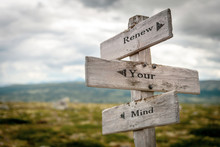 Renew Your Mind Text Engraved On Old Wooden Signpost Outdoors In Nature. Quotes, Words And Illustration Concept.