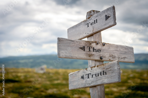 Photo tell the truth text engraved on old wooden signpost outdoors in nature