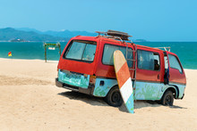 Old Bus In The Sand And A Surfboard On The Beach