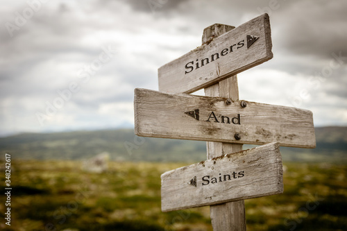 Fotografia sinners and saints text engraved on old wooden signpost outdoors in nature