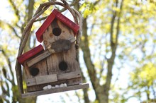 Low Angle View Of Wooden Birdhouse Against Tree