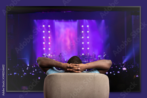 Photo Viewer in front of a large TV relaxed on the armchair at home