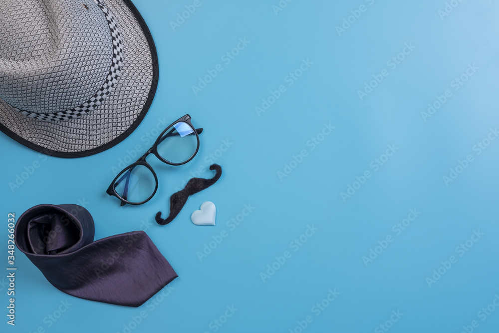 Fototapeta Happy Fathers Day background concept.Decorated hat, eyeglasses,  necktie, mustache light blue heart on light blue pastel background with copy space. Top view, flat lay. - obraz na płótnie