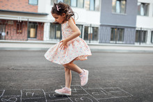 Horizontal Image Of Little Girl Playing Hopscotch On Playground Outdoors. Cute Child Plays Next To The House Oustside. Kid Plays Hopscotch Drawn On Pavement. Summer Activities And Games For Children.