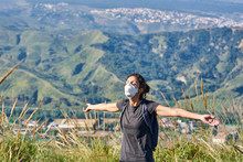 Woman With A Protective Mask Sunbathes In The Field.