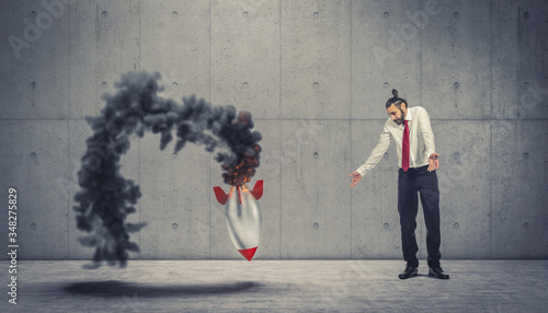 Fototapeta businessman looks at the failure of the takeoff of a vintage rocket with smoke and flames