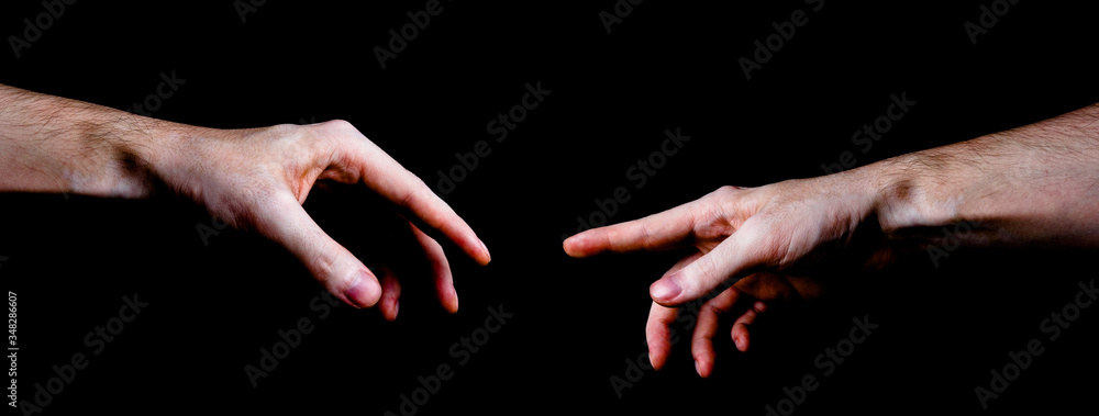 Fototapeta Two male hands trying to touch like a creation of Adam sign isolated on black background. Concept of human relation, community, togetherness, symbolism, culture and history