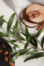 Green Branch On A White Fabric, Cinnamon Sticks, Wooden Stand, Black Plate With Almonds