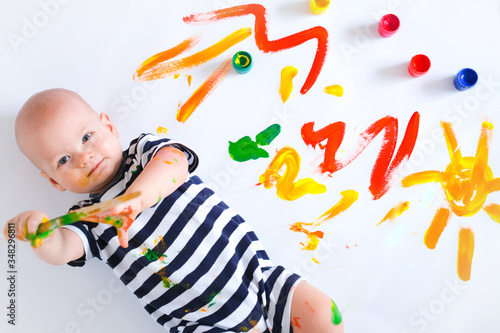 Top view Happy cheerful dirty baby playing with paint and brush on white background Tablou Canvas