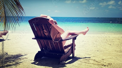 Fotografiet Rear View Of Person Resting On Deck Chair On Beach During Sunny Day