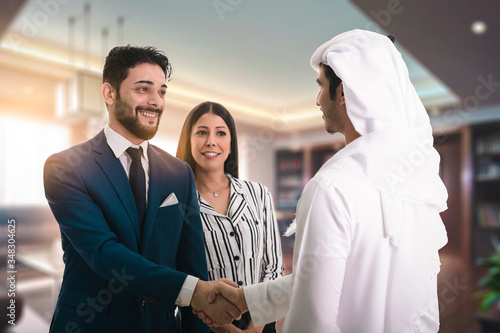 Tablou Canvas Man in suit shake hand of Arabic business man as hello in office