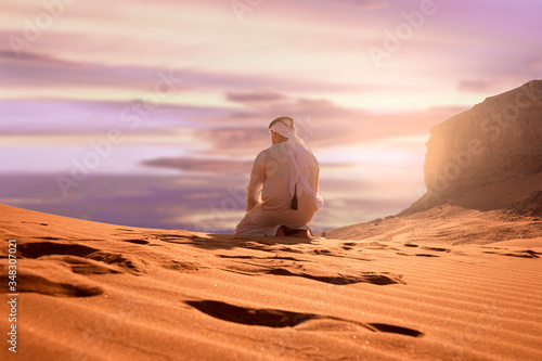 Arabic man with traditional emirates clothes sitting on kness in the UAE desert Canvas Print