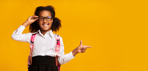 African American Schoolgirl Pointing Finger Aside Over Yellow Background. Panorama