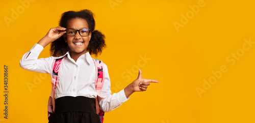 African American Schoolgirl Pointing Finger Aside Over Yellow Background Wallpaper Mural