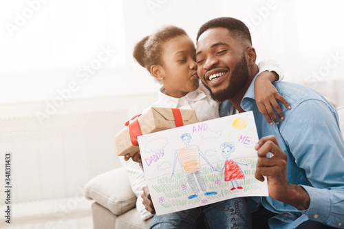 Little girl hugging father and giving handmade drawing - 348311433