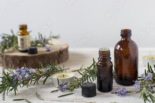 Contenitori di olio essenziale con rametti di rosmarino fioriti Wallpaper Mural