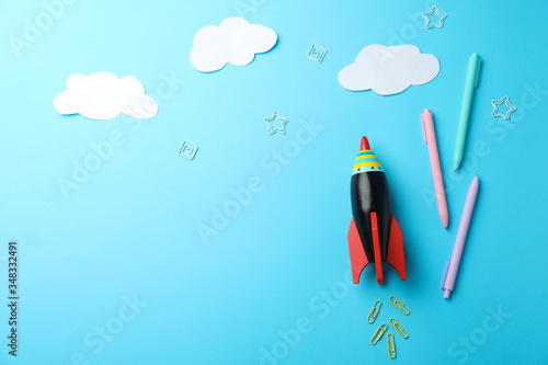 Foto Bright toy rocket and school supplies on light blue background, flat lay