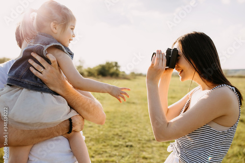 Fototapeta Happy family concept. Mother taking photos of father and little daughter outdoors in a field on summer day. obraz na płótnie