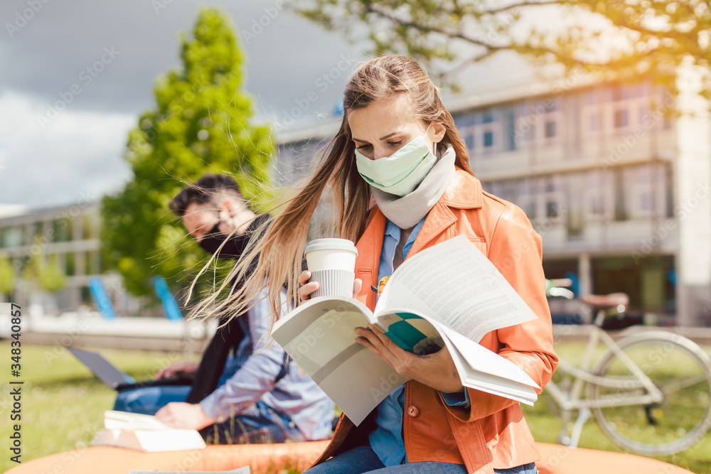 Fototapeta Woman student on college campus learning wearing face mask