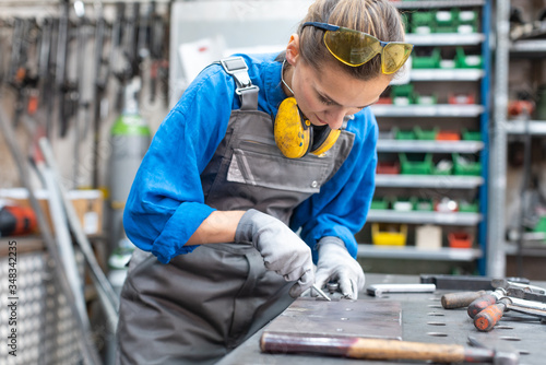 Obraz Sideview of worker woman marking piece of metal - fototapety do salonu