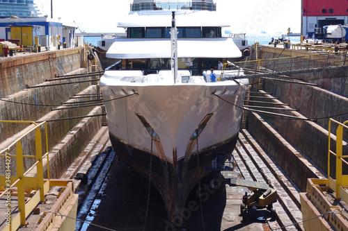 Fotografia, Obraz Photo of ship repairs of yacht in hull in shipyard floating dry dock