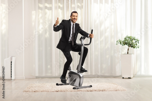 Cuadros en Lienzo Businessman riding an exercise bike at home and showing thumbs up
