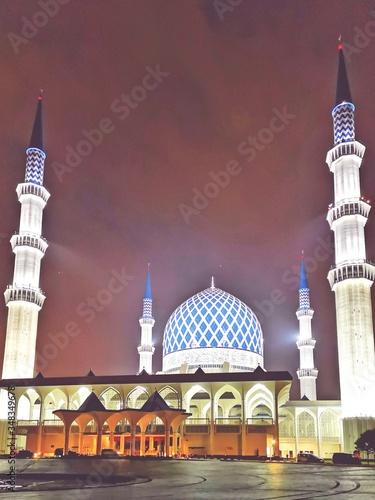 Illuminated Sultan Salahuddin Abdul Aziz Mosque Against Sky In City At Night Wallpaper Mural