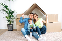 Dreams Come True. A Young Happy Family With Their Little Son Moved To Their New Own Apartment. They Are Sitting On The Floor In An Empty Apartment Near Boxes, And Their Cute Son Is Holding A Flowerpot