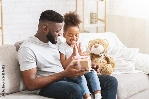 Foto Loving black dad giving present to his little daughter