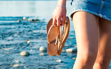 Midsection Of Woman Holding Flip-flop At Beach